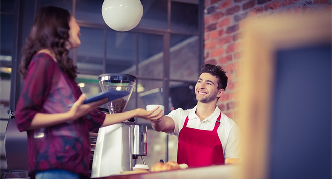 A barista serving a customer in a cafe.png