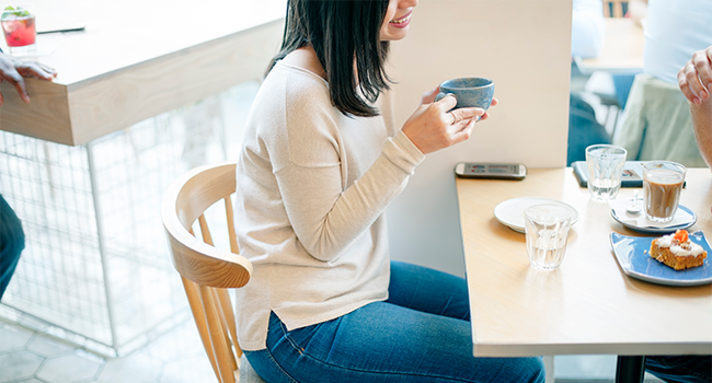 A woman enjoying a cup of coffee in a restaurant.png