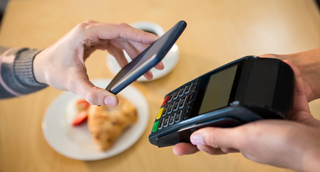 A woman making payment with her phone in a restaurant.png