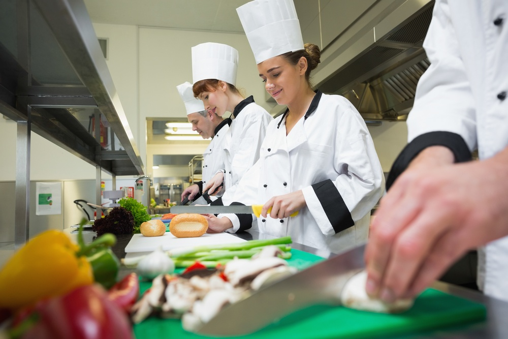 Four chefs preparing food at counter in a row in a professional kitchen.jpeg