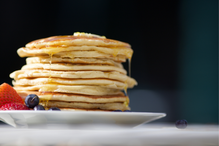 A large stack of pancakes on a ceramic plate
