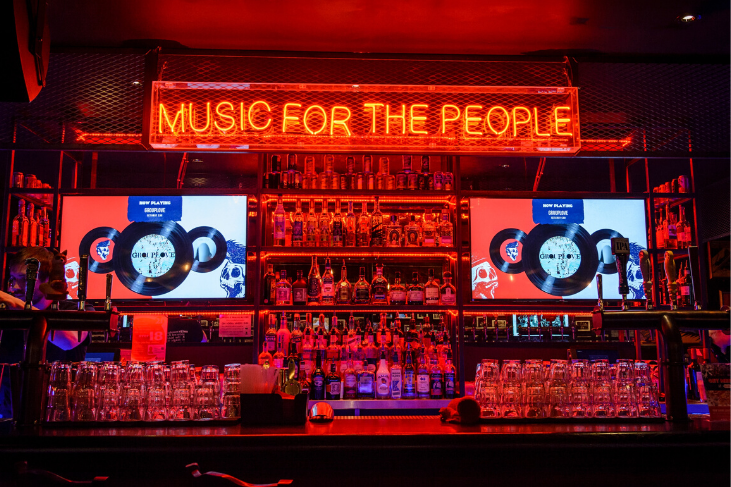 A dark bar with a neon sign that reads 'music for the people'.